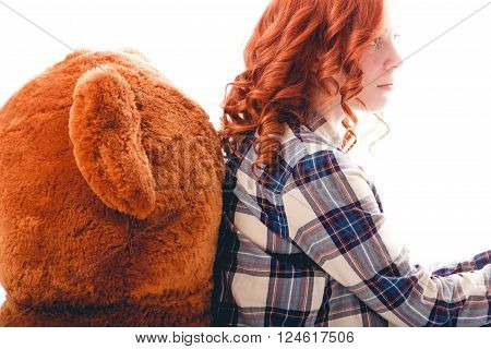 Sad girl sitting against the bear in despair. isolated over white background