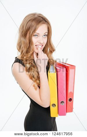 Pensive nervous pretty young businesswoman holding colorful folders and thinking over white background