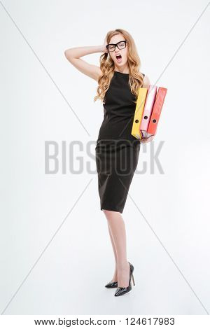 Full length of shocked astonished young business woman standing and holding folders over white background