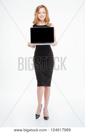 Full length of attractive smiling young businesswoman standing and holding blank screen laptop over white background