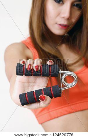 Girl holding gripper in her hand for exerciseing.
