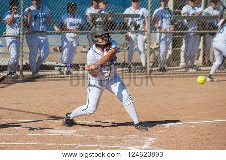 Asian teen softball player taking a swing.