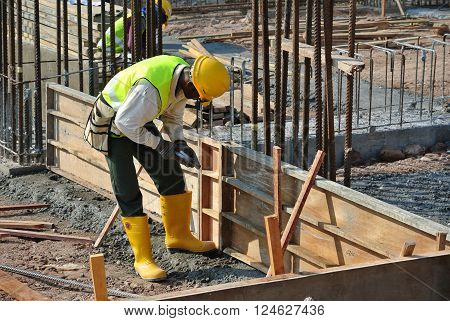 PERAK, MALAYSIA -MARCH 03, 2016: Construction workers fabricating timber form work mostly using plywood at the construction site in Perak, Malaysia.