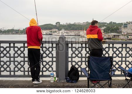 Istanbul Turkey - Jun 28 2015: Two men in Galatasaray football club's jacket were fishing on Galata Bridge in cool early morning with a bag and a chair around.