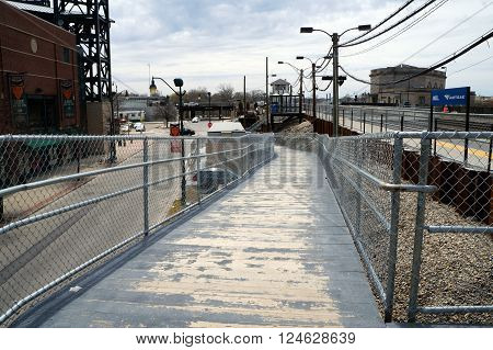 JOLIET, ILLINOIS / UNITED STATES - APRIL 12, 2015: Passengers may ascend a ramp to a railroad platform in downtown Joliet.