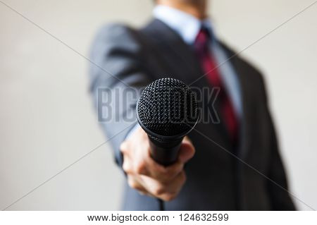 Man In Business Suit Holding A Microphone Conducting A Business Interview, Journalist Reporting, Pub