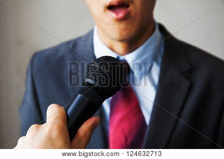 Young Man Feeling Awkward Getting Asked By A Journalist On Isolated White Background