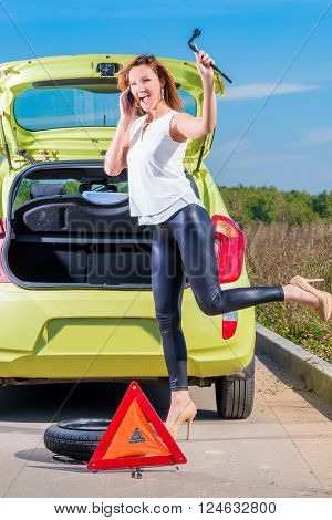 Girl With Phone And Wrench Is Waiting Roadside Assistance