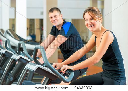 Portrait Of A Happy Couple On A Stationary Bike In The Gym
