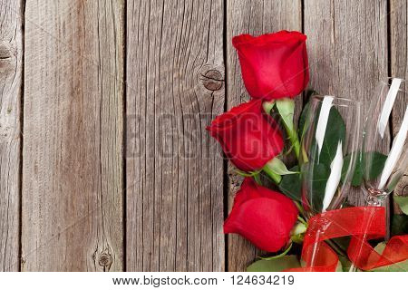 Valentines day roses bouquet and champagne glasses on wooden table. Top view with copy space