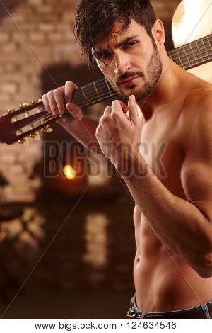 Handsome young man holding guitar, bare upper body.