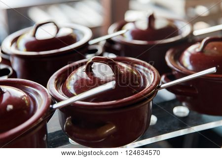 cooking, culinary, eating and asian kitchen concept - close up of hot food pots at restaurant