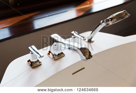 sanitary, plumbing and washing concept - close up of bath tap and shower at bathroom