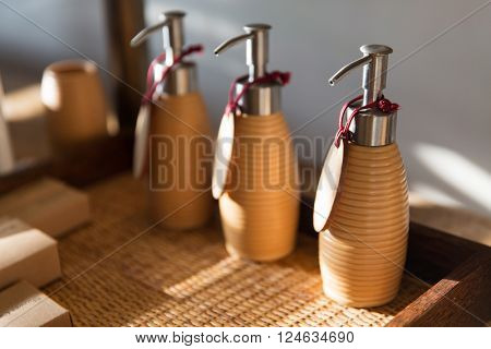 beauty, body care, luxury, natural cosmetics and hygiene concept - close up of liquid soap or body lotion set at hotel bathroom