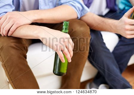 friendship, leisure, people and alcohol concept - close up of male friends drinking beer at home