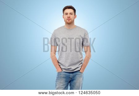 male, gender, fashion and people concept - young man in gray t-shirt and jeans over blue background