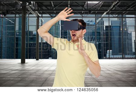 3d technology, virtual reality, entertainment and people concept - scared young man with virtual reality headset or 3d glasses playing game over empty industrial room and city panorama background