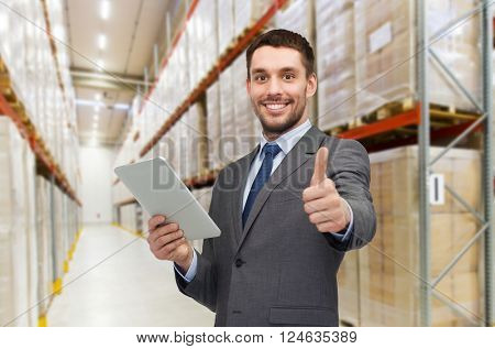 wholesale, logistic business, export, technology and people concept - smiling businessman with tablet pc computer showing thumbs up over warehouse background