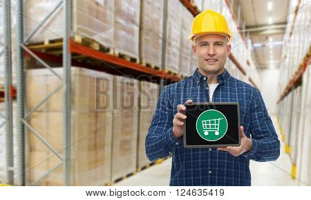 wholesale, logistic, business, export and people concept - happy man or manager showing tablet pc computer with shopping cart on screen over warehouse background
