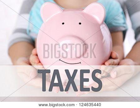 Tax Concept. Savings concept. Hands holding piggy bank, close up