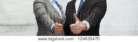 business, people and gesture concept - close up of businessman and businesswoman showing thumbs up over gray concrete wall background