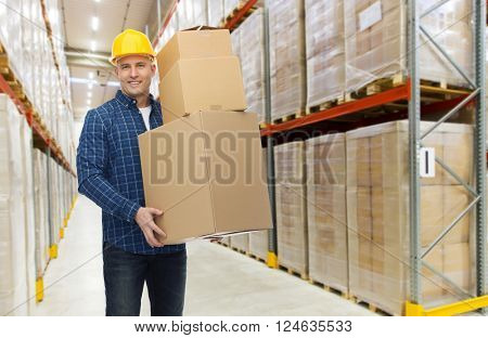 wholesale, logistic, business, export and people concept - happy man or loader in helmet with cardboard box over warehouse background