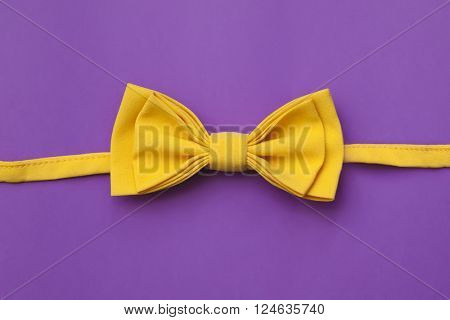 yellow bow tie on a purple background