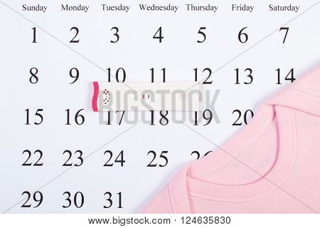 Pregnancy test with positive result and bodysuit for newborn on calendar concept of extending family and expecting for baby