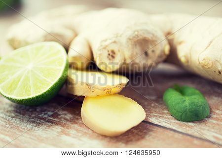 ethno science, culinary, diet, eco food and objects concept - close up of ginger root and lime slices on wooden table