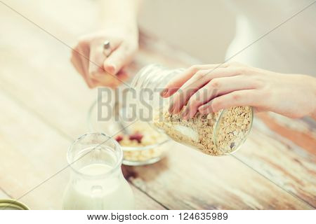 food, healthy eating, people and diet concept - close up of woman eating muesli with milk for breakfast
