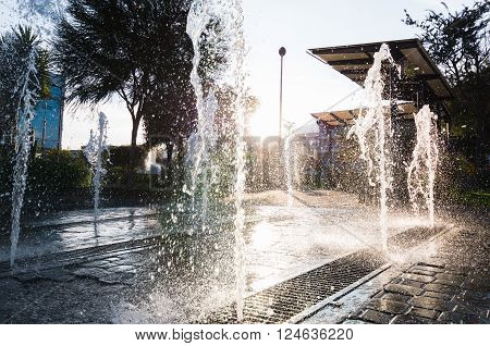 Modern and beutifull waterfall with sun in the back. Water drops dancing in a big splash with threes in the back