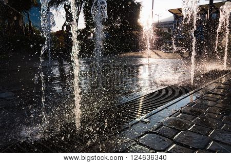 Modern and beutifull waterfall with sun in the back. Water drops dancing in a big splash