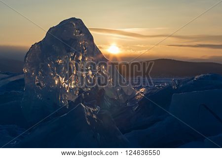 Sun rises over the ice floes. Beautiful winter landscape in the Lake Baikal.