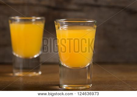 Two shot glasses of vodka with orange juice over wooden background