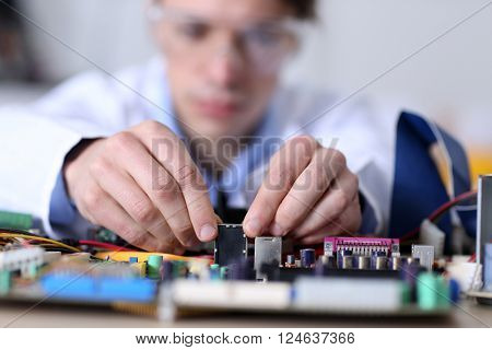 Young man in glasses repairing computer hardware in service center