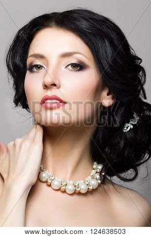Portrait of beautiful aristocratic woman touching her neck. Bridal makeup and coiffure. Modern makeup. Studio shot