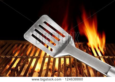 Spatula Made From Stainless Steel Close Up. Flaming Barbecue Grill In The Background