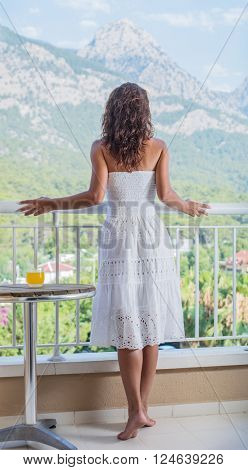 Woman is on the hotel balcony. Green nature on the background.