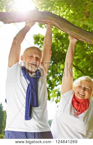 Old man and senior woman doing sports in nature hanging on a tree