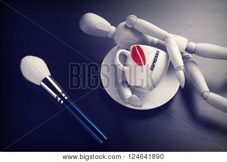 Empty Coffee Cup Makeup Powder Brush and Wooden Man's Figurine On Black Wood Background Close-up Concept For Beauty Dating Flirting Top View Tonned