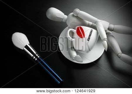 Makeup Brush,  Coffee Cup And Man's Figurine On Black Background