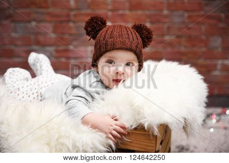 Adorable baby in brown knitted hat sitting in wooden box with fluffy plaid against brick wall background