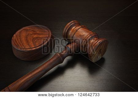 Auctioneer Or Judges Hammer On The Black Table In Dark