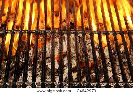 Overhead View Of Empty BBQ Hot Fire Grill And Burning Charcoal Briquettes With Bright Flames. Outdoor Scene. Concept for Summer Party Or Picnic Or Cookout. Isolated Black Background. Close Up