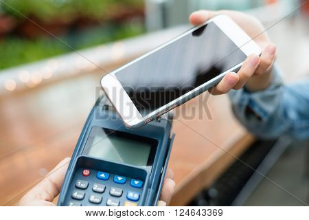 Woman using cellphone for payment by NFC technology