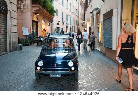 ROME-AUGUST 6: Tourists and traffic on the narrow street on August 62013 in Rome Italy. Rome is the capital of Italy and also of the homonymous province and of the region of Lazio.