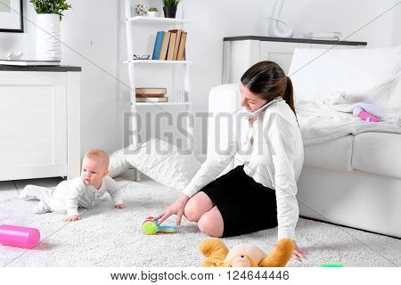 Businesswoman with baby boy on couch working from home using mobile phone