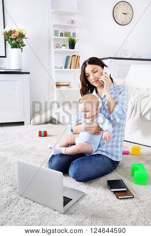 Beautiful woman with baby boy working from home using laptop