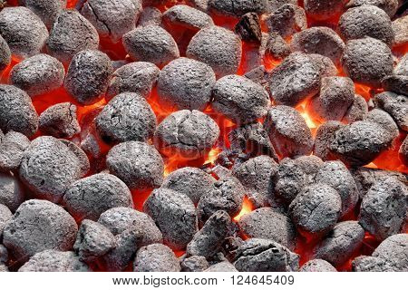 BBQ Grill Pit With Glowing And Flaming Hot Charcoal Briquettes Food Background Or Texture Close-Up Top View