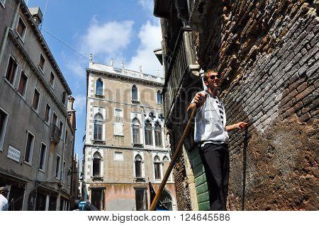 VENICE-JUNE 15: Gondolier runs the gondola on the Venetian canal on June 15 2012 in Venice Italy.
